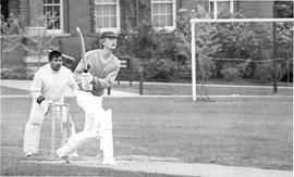 Two unidentified men playing cricket