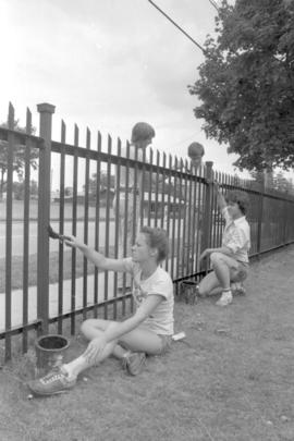 Youth Painting Cemetary Fence