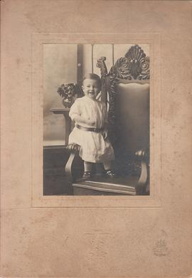 Photograph of toddler standing on chair