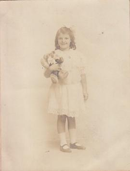 Photograph of girl holding teddy bear