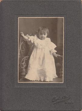 Photograph of baby standing on chair